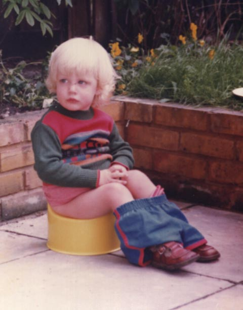 Blonde child on sitting on a potty, outdoors